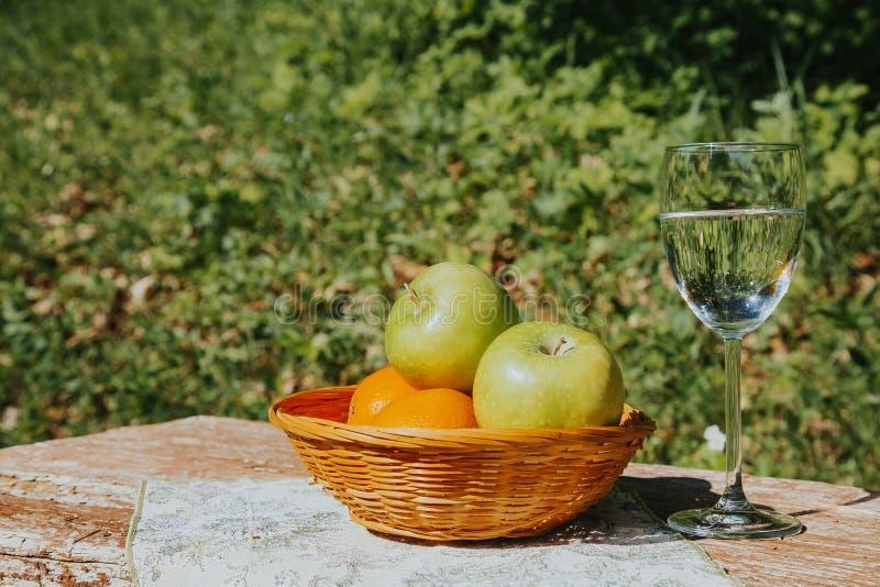 Ein Glas frisches Apple-Wasser und -?pfel in einem Korb auf einem Holztisch lizenzfreie stockfotografie
