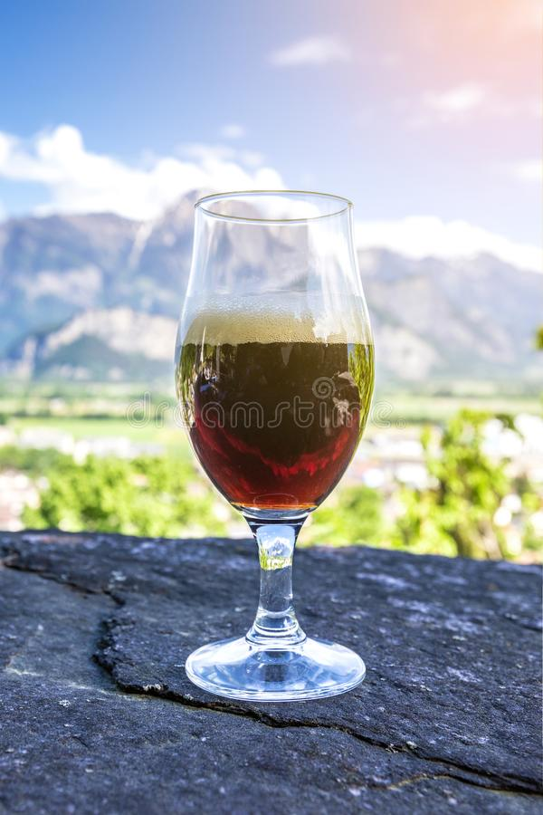 Ein Glas frisches Bier auf dem Hintergrund der Berge stockfoto
