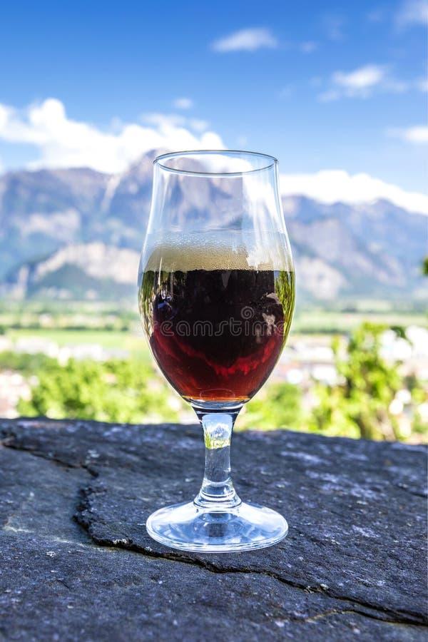 Ein Glas frisches Bier auf dem Hintergrund der Berge stockfotografie