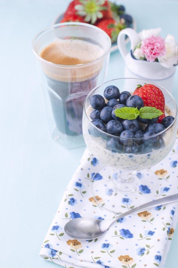 Ein Glas Kaffee und Pudding chia mit Blaubeeren und Erdbeeren für vegetarisches gesundes Lebensmittel des Frühstücks Hintergrund  stockfotos