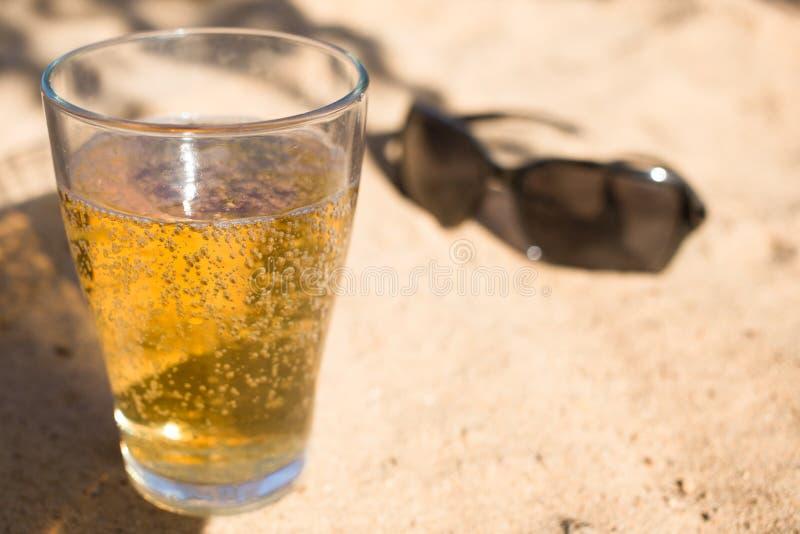 ein Glas kaltes Bier und Sonnenbrille auf dem Strandsand stockfotos