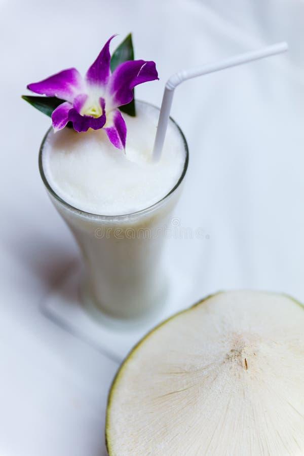 Ein Glas Kokosnuss Smoothies mit Kokosnuss lizenzfreie stockfotografie