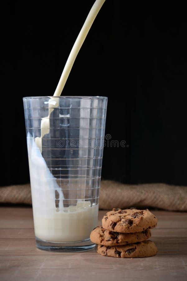 Ein Glas Milch und Plätzchen mit Schokoladensplittern lizenzfreie stockbilder