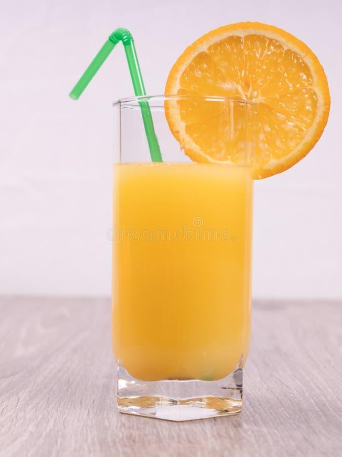 Ein Glas mit einem Stroh verziert mit einer Scheibe der Orange auf einem hellen Hintergrund stockfoto