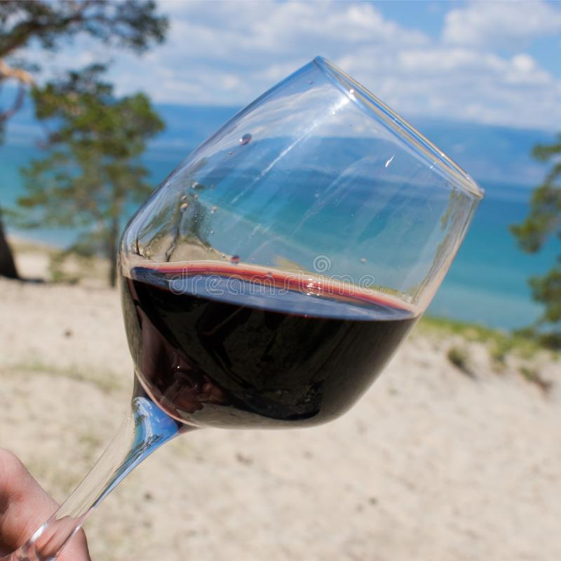 Ein Glas Rotwein gegen den blauen Himmel und den Wald lizenzfreie stockfotografie