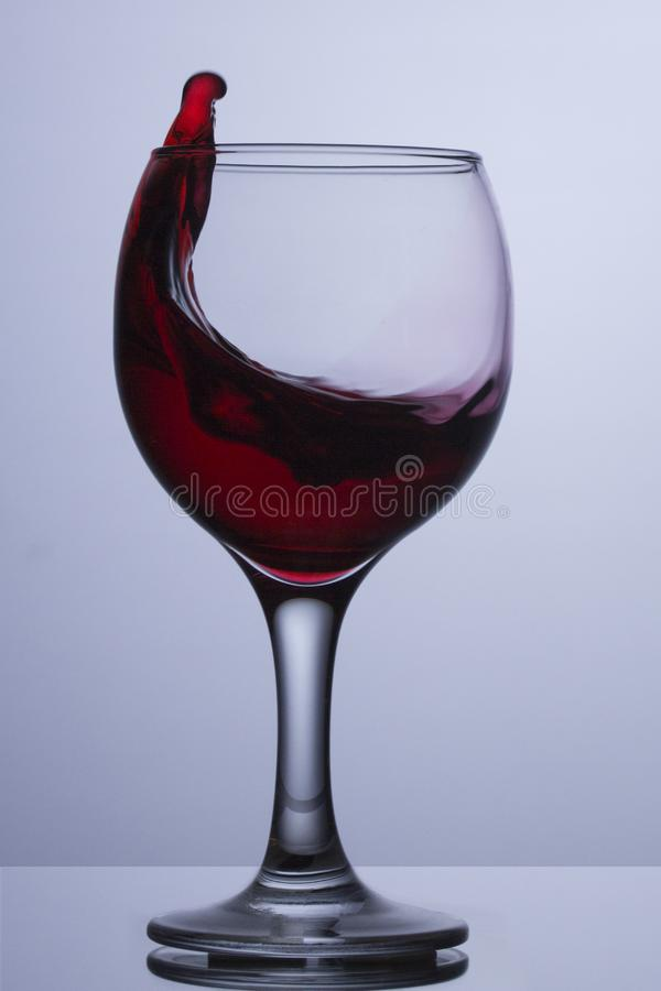 Ein Glas Rotwein mit einer Welle Rotwein wird aus einem Glas ringsum transparente Glasgläser heraus gespritzt lizenzfreie stockfotografie