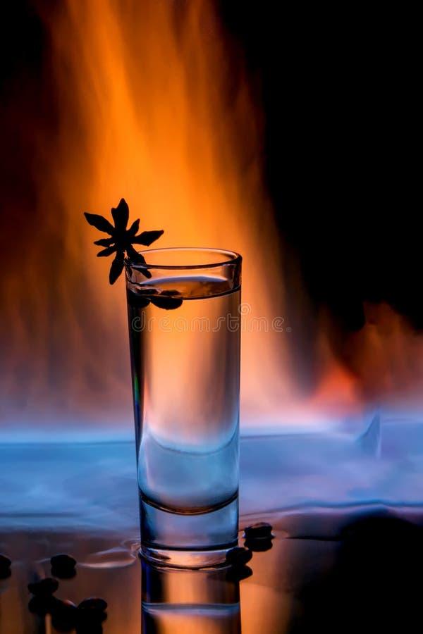 Ein Glas sambuca auf Feuer mit brennendem sambuca, Kaffeebohnen und Anisstern auf einem schwarzen Hintergrund lizenzfreie stockbilder