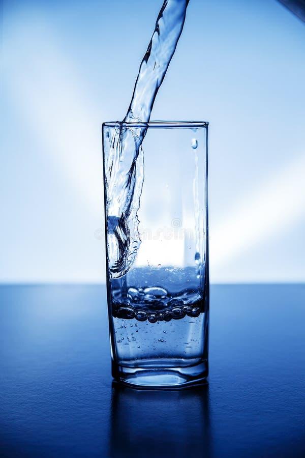 Ein Glas sauberes Trinkwasser belichtet mit Blaulicht stockbilder