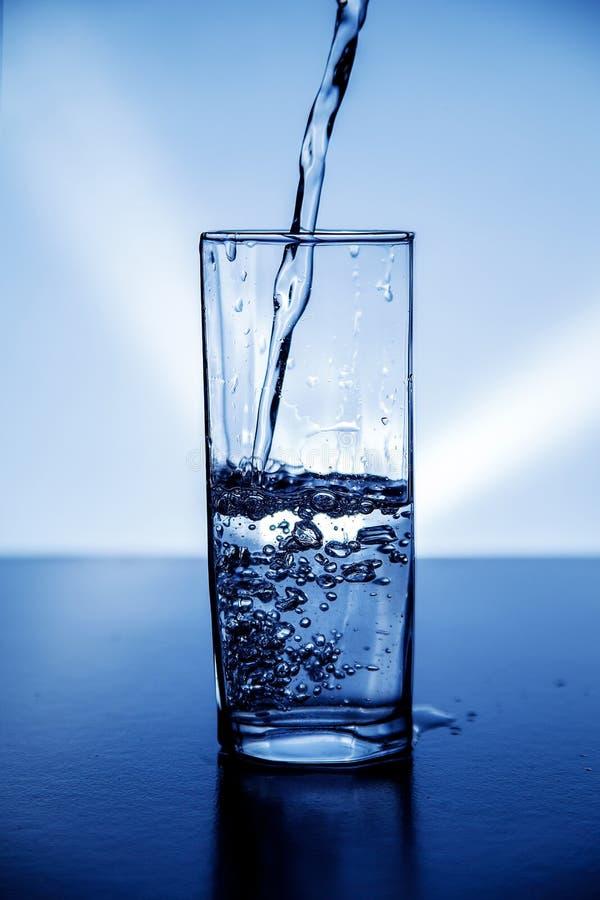 Ein Glas sauberes Trinkwasser belichtet mit Blaulicht lizenzfreie stockfotografie