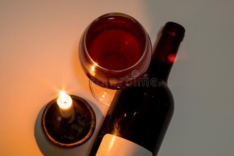 Ein Glas und eine Flasche Rotwein nahe bei einer brennenden Kerze stockbilder