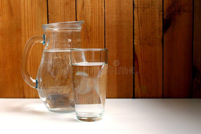 Ein Glas und ein Krug Wasser auf einer Tabelle lizenzfreie stockbilder