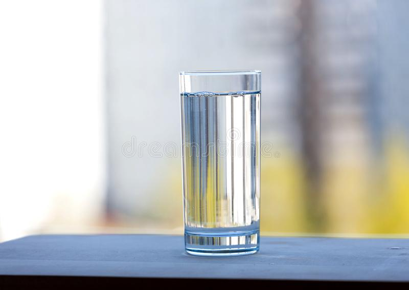 Ein Glas voll vom Trinkwasser draußen Sonniger Tag des Sommers stockfoto