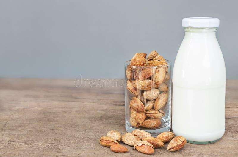Ein Glas von Mandeln und von Flasche Milch auf dem Holztisch stockfotografie