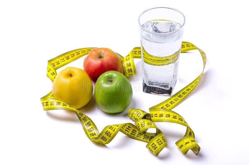 Ein Glas Wasser und Äpfel: grün, rot, gelb mit einem Messen lizenzfreies stockfoto