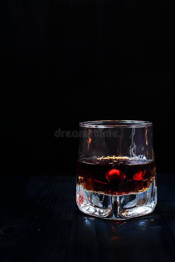 Ein Glas Whisky auf einem schwarzen Hintergrund und einem Holztisch lizenzfreie stockfotos
