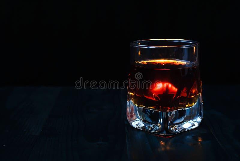 Ein Glas Whisky auf einem schwarzen Hintergrund und einem Holztisch lizenzfreies stockbild