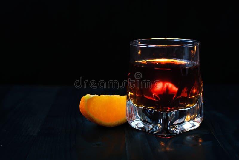 Ein Glas Whisky mit einer orange Scheibe auf einem schwarzen Hintergrund und einem Holztisch lizenzfreie stockbilder