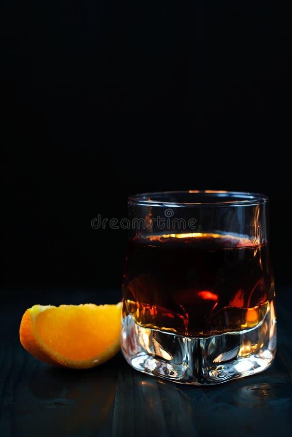 Ein Glas Whisky mit einer orange Scheibe auf einem schwarzen Hintergrund und einem Holztisch lizenzfreie stockfotos