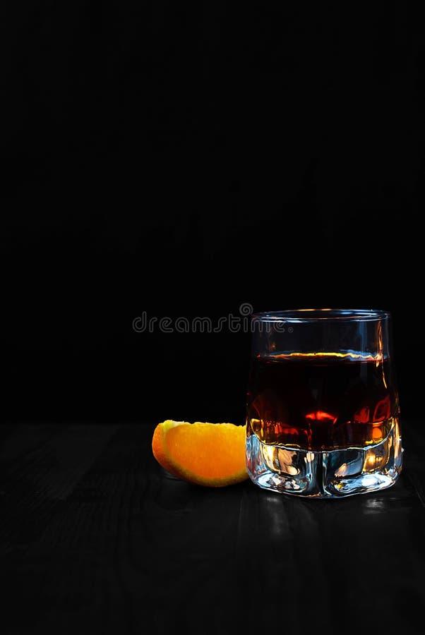 Ein Glas Whisky mit einer orange Scheibe auf einem schwarzen Hintergrund und einem Holztisch lizenzfreies stockfoto