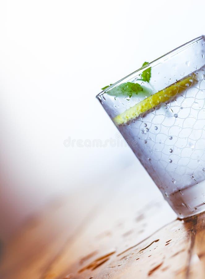 Ein Glasbecher und ein Krug kalte Limonade auf einem wei?en h?lzernen Hintergrund umgeben durch Zitronen stockfotografie