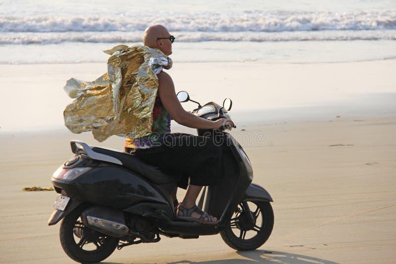 Ein glatzköpfiger Mann fährt auf einen Roller entlang der Küste oder dem b stockbilder