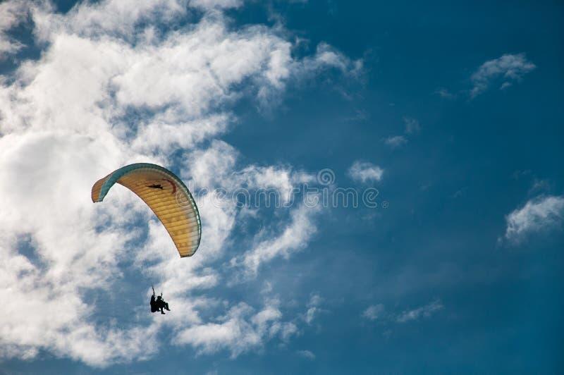 Ein Gleitschirmfliegen im blauen Himmel vor dem hintergrund der Wolken Gleitschirmfliegen im Himmel an einem sonnigen Tag stockbild