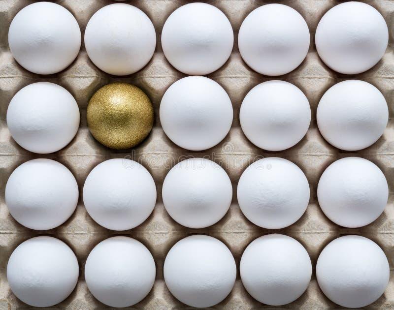 Ein goldenes Ei unter weißen Eiern in einem Kartoneikasten stockfotografie