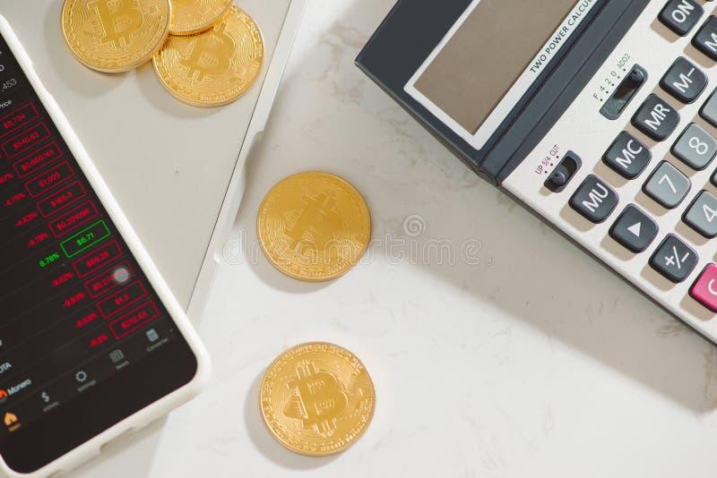 Ein goldenes körperliches Bitcoin auf einem Smartphone ` s Schirm, Stapel coi lizenzfreie stockfotografie