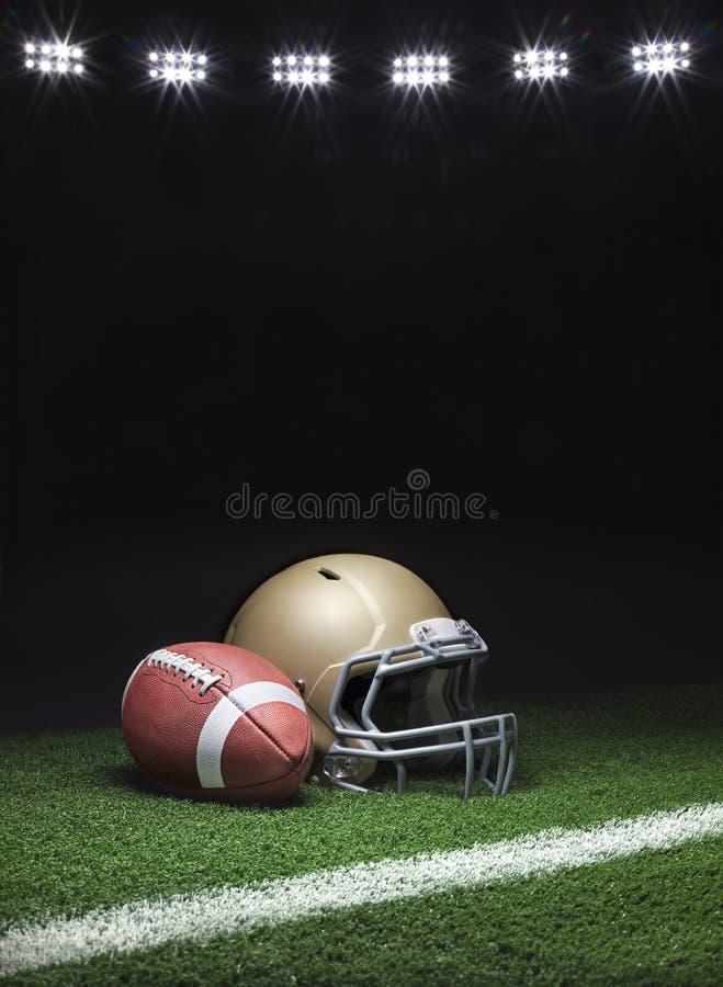 Ein Goldfußball-Helm und Fußball auf einem Grasfeld mit Streifen auf dunklem Hintergrund mit Lampenlichter stockbild