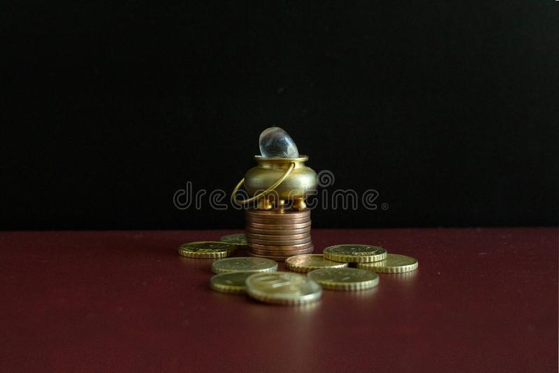 Ein Goldschatz und ein Kristallstein auf Münzen eines Stapels stockbild