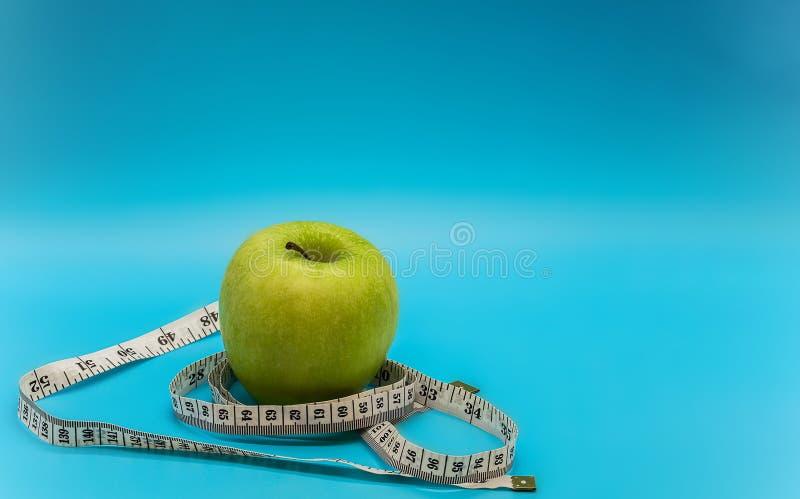 Ein grüner reifer saftiger Apfel und ein weißes messendes Band um es auf einem sauberen hellblauen Hintergrund mit Raum für Wrigh stockbilder