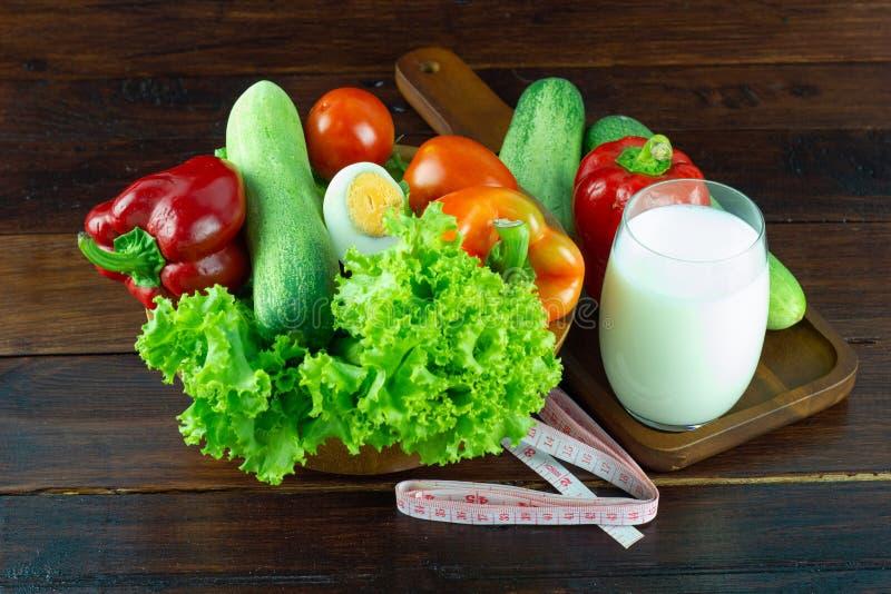Ein grüner Salat in der hölzernen Schale, die aus einer Mischung mit Milch in einem Glas besteht lizenzfreies stockfoto