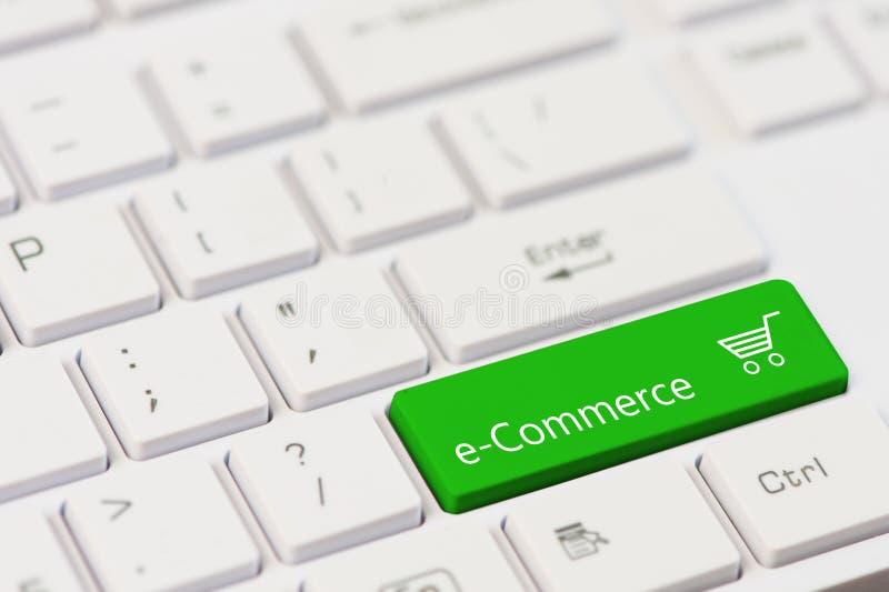 Ein grüner Schlüssel mit Text des elektronischen Geschäftsverkehrs auf weißer Laptoptastatur lizenzfreie stockfotografie