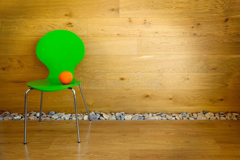 Ein grüner Stuhl und ein orange/moderner Innenraum lizenzfreie stockbilder