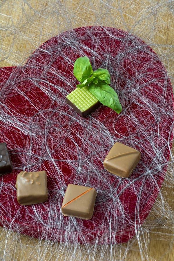 Ein grünes Bonbon mit Schokolade auf dem roten Hintergrund stockfotos