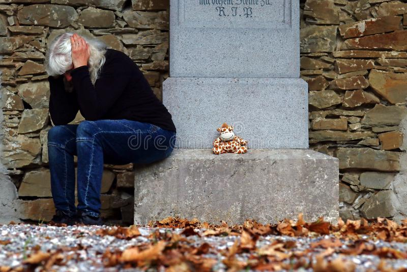 Ein Grabstein mit Spielwaren und einer traurigen Frau lizenzfreies stockbild