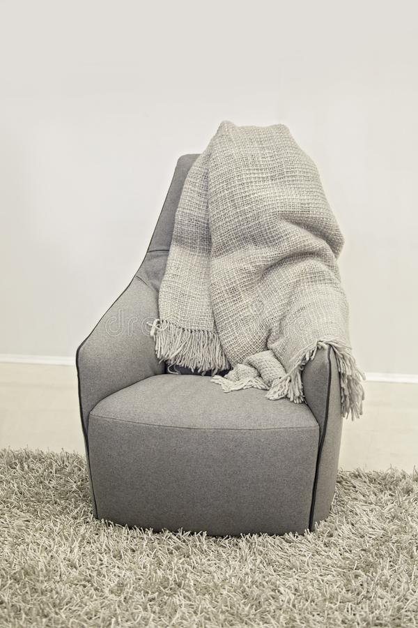 Ein grauer gemütlicher Lehnsessel mit einer Wolldecke im Schlafzimmer auf einem Stapelteppich Innenraum in der Skaninavian-Art stockfotos