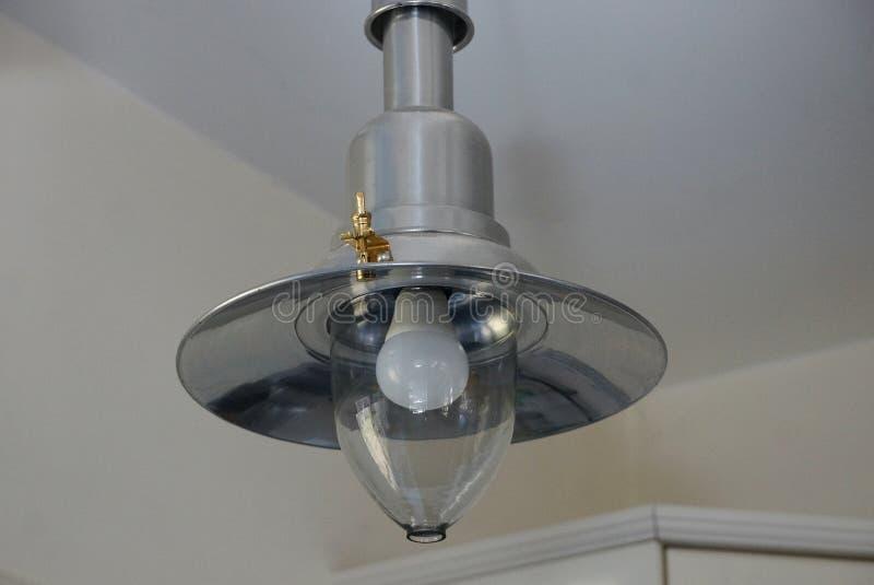 Ein großer grauer Leuchter mit einem Metall und Glasglühlampe auf der weißen Decke im Raum lizenzfreie stockfotos
