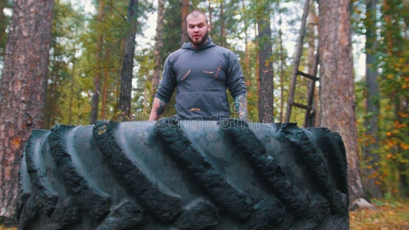 Ein großer männlicher Bodybuilder in der Nähe des Reifens lizenzfreies stockbild