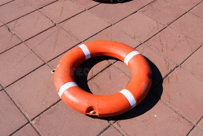 Ein großer runder orange Plastikrettungsring für Sicherheits- und Rettungsleute im Wasser liegt auf dem Steinboden stockfotos