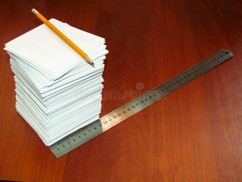 Ein großer Stapel von quadratischen weißen Blättern, von Machthaber und von Bleistift liegt auf einer braunen Tabelle lizenzfreies stockfoto