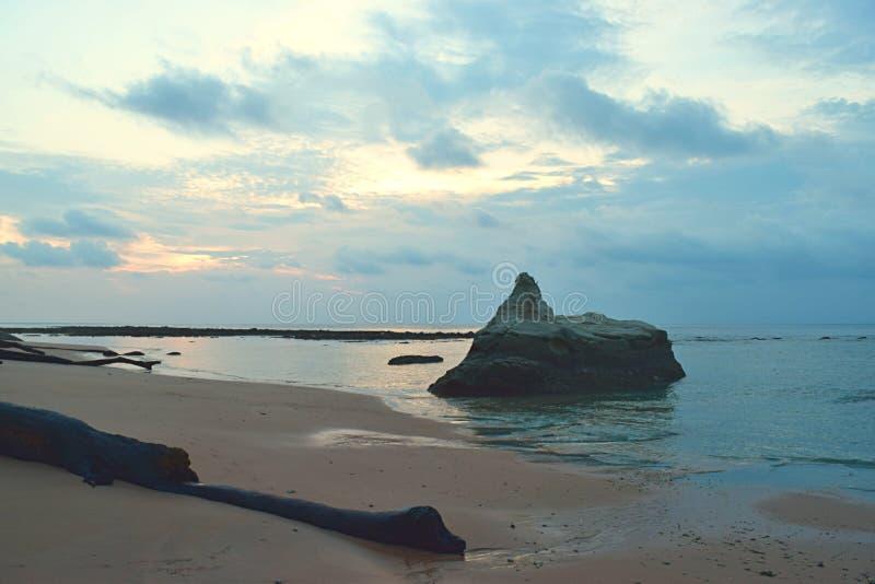 Ein großer Stein im Wasser des ruhigen Sees bei ursprünglichem Sandy Beach mit Farben im Morgen-bewölkten Himmel - Sitapur, Neil  stockbilder