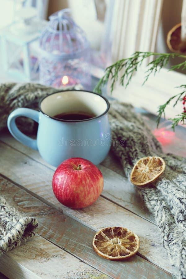 Ein großer Tasse Kaffee, ein Apfel, ein gestrickter woolen Schal auf einem Holztisch mit Weihnachtsdekor, brennende Kerzen, Tanne stockfotos