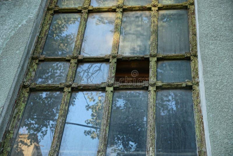 Ein großes altes graues grünes Fenster auf der Wand des Gebäudes stockbild