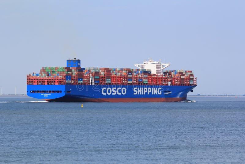 Ein großes blaues Frachtschiff steuert durch das Meer im Sommer lizenzfreie stockfotos