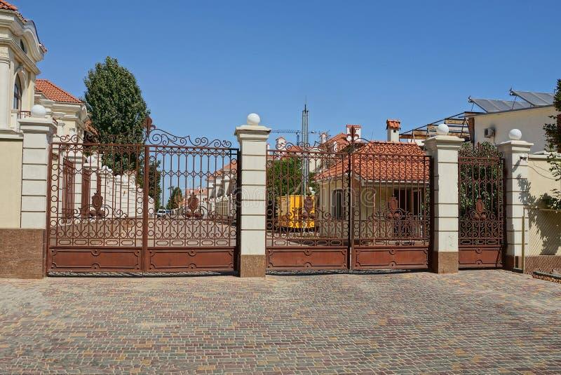Ein großes braunes Metalltor und eine Tür auf der Straße auf dem Bürgersteig stockfotos