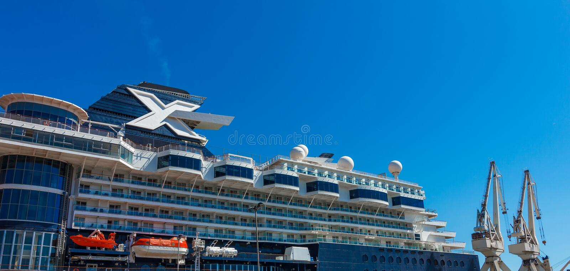 Ein großes Luxuskreuzfahrtschiff festgemacht hinter Hafenkran lizenzfreie stockfotografie