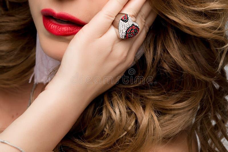 Ein großes Porträt der Lippen und der Hand einer Frau mit dem Ring Ring mit Edelsteinen, Silber und Rot Gesicht, rote Lippen lizenzfreies stockbild