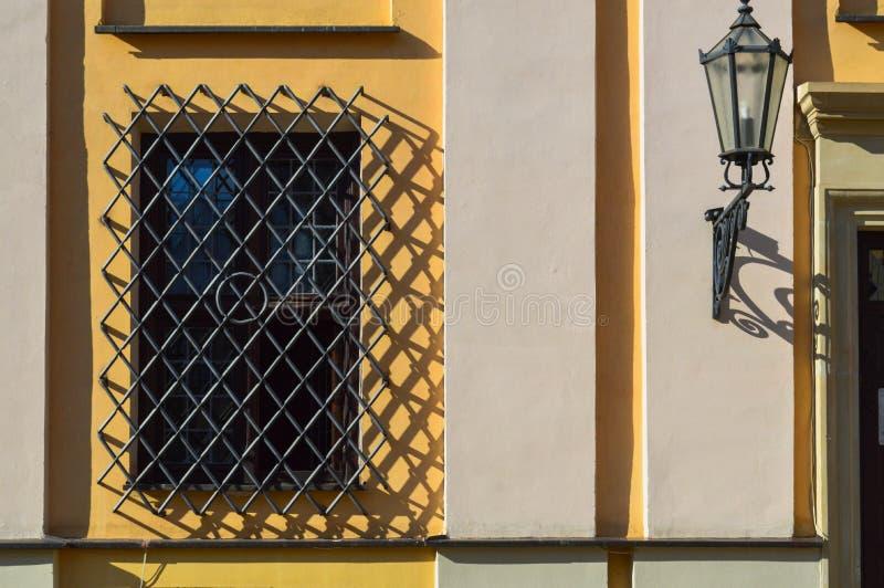 Ein großes rechteckiges Fenster eines gelben Steingebäudes schloss durch ein großes schwarzes Eisengitter Der Hintergrund lizenzfreie stockfotografie