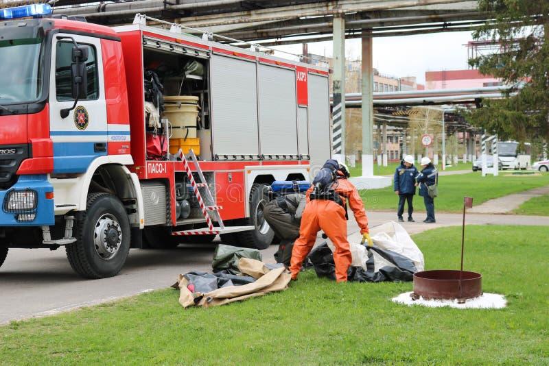 Ein großes Rettungsfahrzeug des roten Feuers, ein LKW, zum eines Feuers auszulöschen und Mannesfeuerwehrmänner werden vorbereitet stockfotos